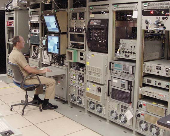 A submarine radio room with racks of equipment, and a military PDU at the top of each rack.